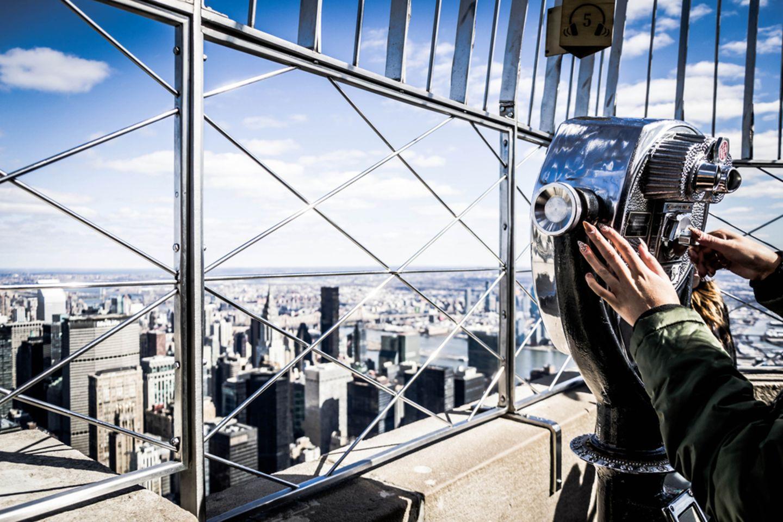 Die teuersten Touristenattraktionen weltweit: Frau steht an Teleskop und blickt über Manhattan, New York City
