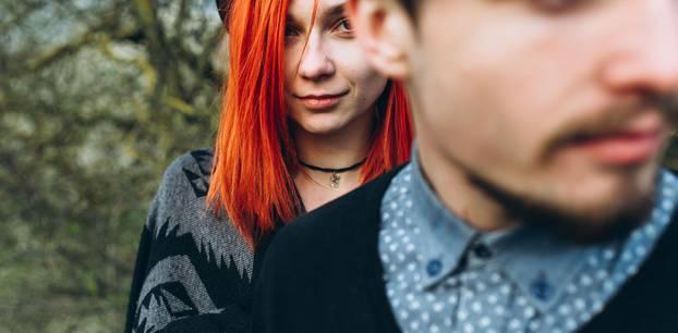 Was sollte eine Beziehung uns bringen? Eine Frau steht hinter ihrem Partner und guckt geheimnisvoll