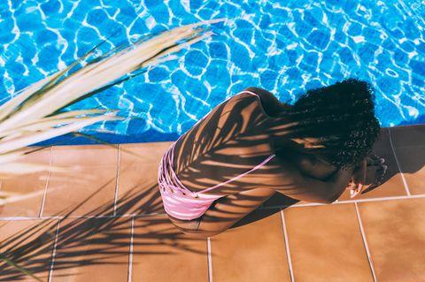 Sonnenstich-Behandlung: Frau im Schatten einer Palme