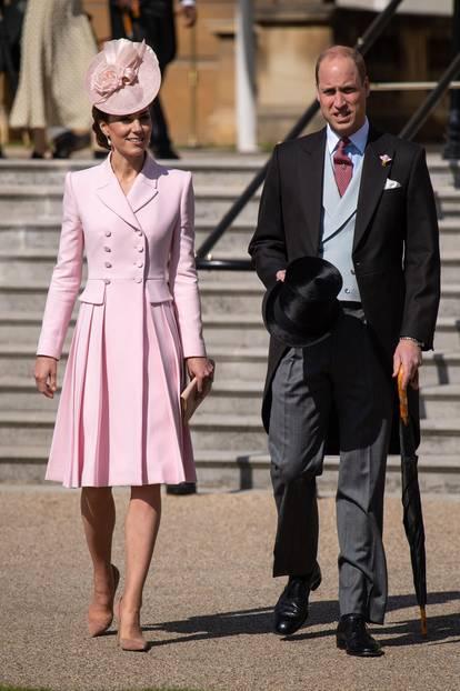 """In Sachen royale Auftritte ist Kate schon jetzt eine wahre Königin. Zur Royal Garden Party erscheintdie Herzogin an der Seite ihres Ehemannes Prinz William in einem rosafarbenen Mantelkleid von Lieblingsdesigner Alexander McQueen – und zieht darin alle Blicke auf sich. Der gleichfarbige Fascinator und die nudefarbenen Accessoires ergänzen den Look, wirklich perfekt machen ihn aber erst die tropfenförmigen """"Collingwood Pearl""""-Ohrringe, die einst Prinzessin Diana gehörten. We are in love!"""
