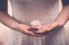 Warum ist es so schwer loszulassen? Eine Frau hält eine Blume in ihren Händen
