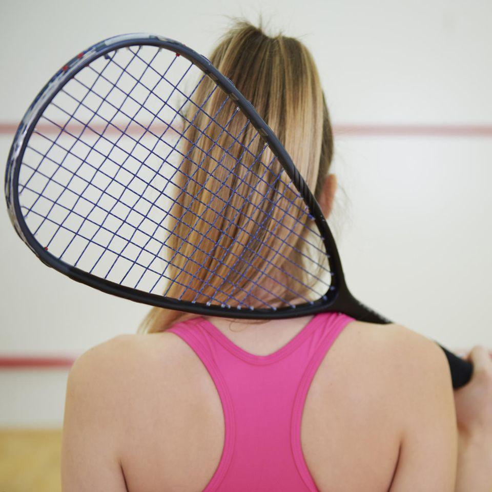 Sexismus: Frau von hinten mit Squash-Schläger in der Hand