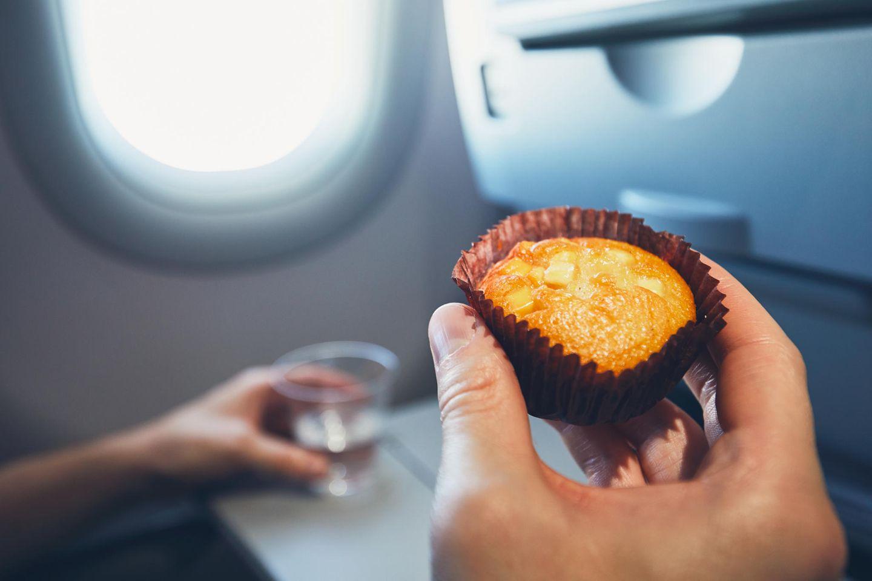 Darf man Essen mit ins Flugzeug nehmen? Was erlaubt ist: Mensch mit Muffin in der Hand sitzt im Flugzeug