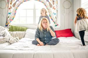 Elternlügen: Eine müde Mama auf dem Bett, ihre Kinder turnen um sie herum