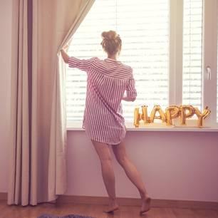 Wie glücklich bin ich? Eine Frau schiebt im Pyjama den Vorhang zur Seite