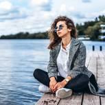 ElitePartner-Studie: Eine nachdenkliche Frau sitzt auf einem Steg am See