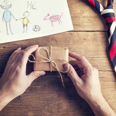 Vatertagsgeschenke: Männerhände packen ein kleines Päckchen aus