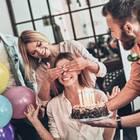 Überraschungsparty: Tipps, wie der Plan aufgeht! Frau werden die Augen zugehalten, vor ihr eine Geburtstagstorte mit Kerzen