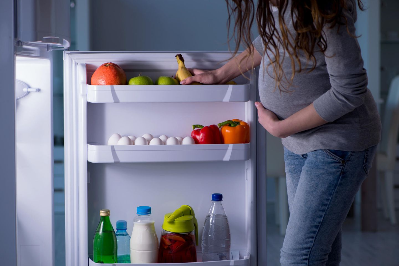 Was dürfen Schwangere nicht essen: Schwangere Frau am Kühlschrank