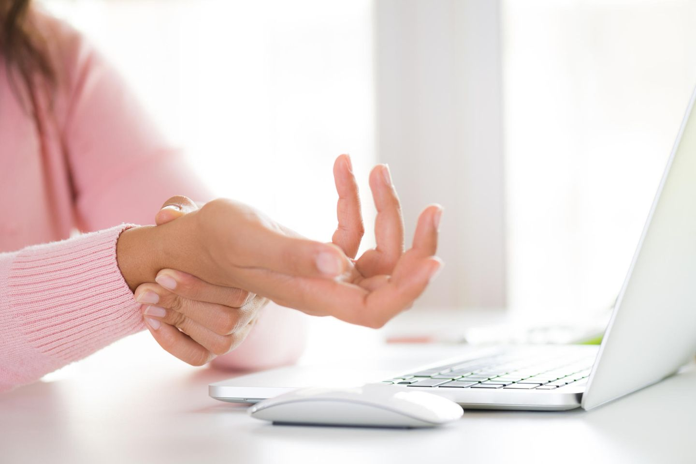 Arthrose: Frau umfasst schmerzendes Handgelenk