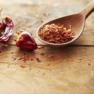 Peperoni trocknen: Methoden und praktische Tipps: Getrocknete Peperonischoten neben einem Holzlöffel mit Peperoni-Flocken