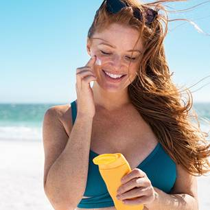 Lichtschutzfaktor 100: Frau trägt Sonnencreme im Gesicht auf