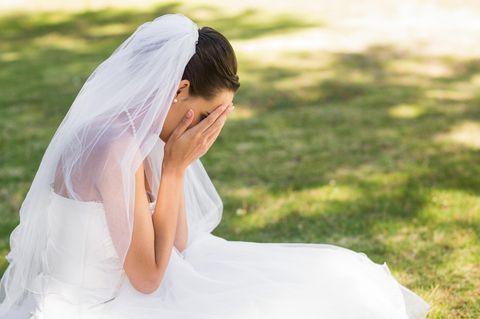 Erfahrungsbericht: Weinende Braut kniet auf einer Wiese
