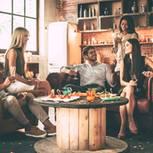 Cocooning: Was hinter dem Wohntrend steckt: Gruppe junger Menschen sitzen um einen Tisch herum und unterhalten sich