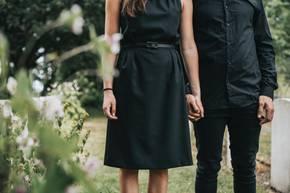 Wenn das eigene Kind stirbt: Eltern Hand in Hand in schwarzer Kleidung