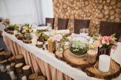 Hölzerne Hochzeit: Bedeutung, Deko und Geschenkideen: Gedeckte Tafel mit Holzscheiben, Blumen und Geschirr