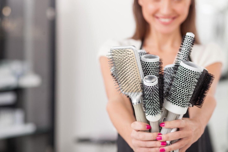 Haarbürste reinigen in drei Schritten: Frau hält viele Haarbürsten in der Hand