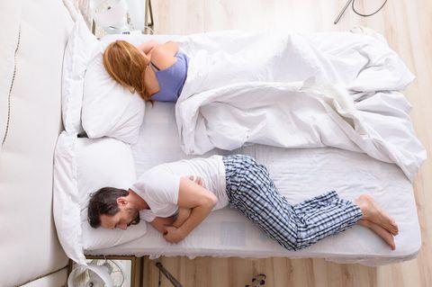 Beziehung ohne Sex: Paar im Bett mit dem Rücken zueinander