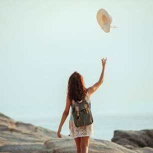 Routine durchbrechen: Frau wirft Hut in die Luft