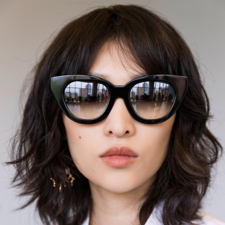 Übergangsfrisuren: Frau mit Sonnenbrille und mittellangen Haaren und curtain bangs