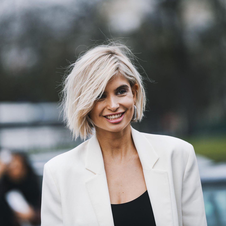 Übergangsfrisuren: Frau mit kinnlangen Haaren lächelt