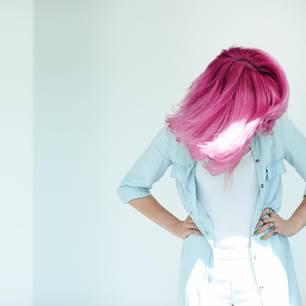 Haare entfärben: Die besten Tipps und Hausmittel: Frau mit rosafarbenen Haaren schüttelt ihr Haar nach vorne