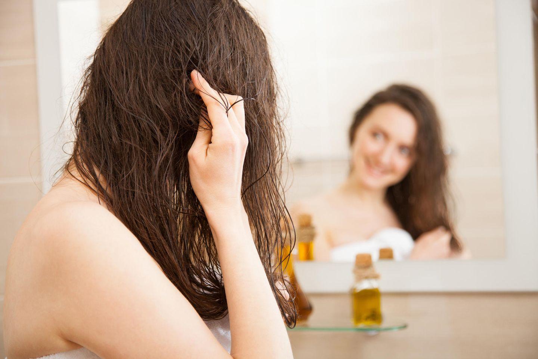 Olivenöl für die Haare: Frau steht vor dem Spiegel und massiert Olivenöl in die Haare ein