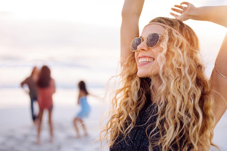 Egoistische Mutter: Frau tanzt an Strand