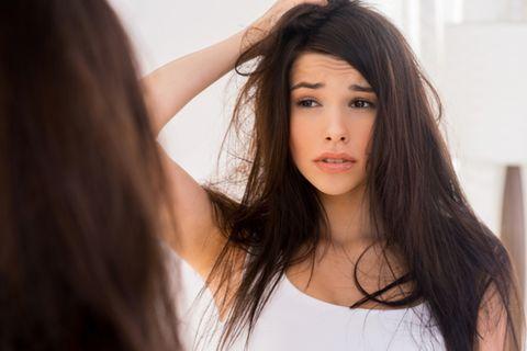 Verfilzte Haare: 6 effektive Tipps für kämmbares Haar: Frau fasst sich in die langen Haare und schaut unglücklich in den Spiegel