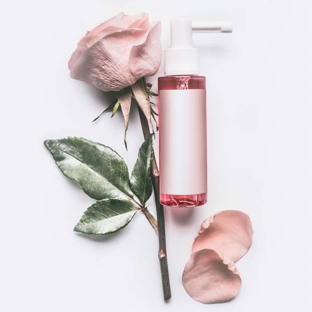 Rosenwasser: Rose auf weißem Tisch und ein Pumpspender mit Rosenöl