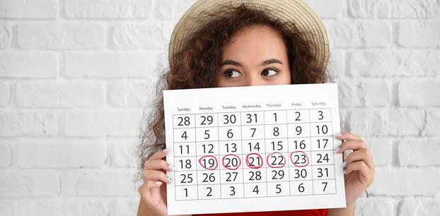 Periode bleibt aus: Frau hält Zykluskalender hoch