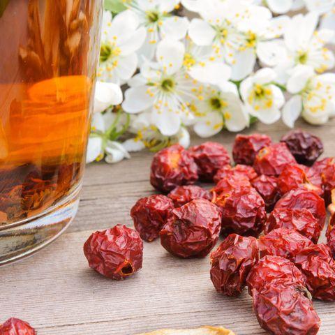 Hagebutten trocknen: So geht's richtig: Getrocknete Hagebutten vor einem Glas Tee, daneben Blüten