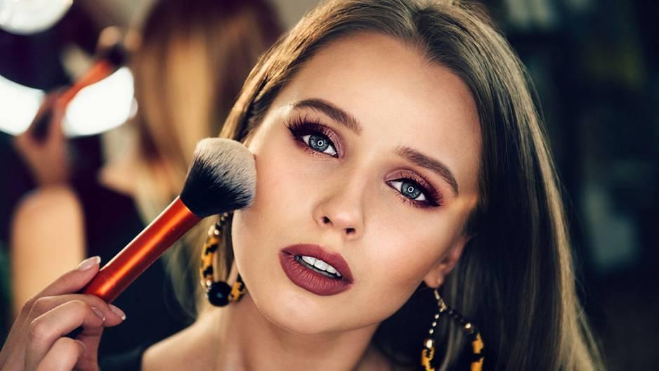 Abend-Make-up: 5 Steps zum perfekten Look: Frau hält sich Schminkpinsel ins Gesicht