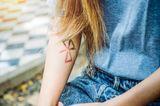 Tattoo am Arm: Dezentes Symbol am Arm