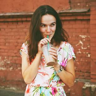 Horoskop: Junge Frau trinkt Kaltgetränk mit Strohalm und lächelt dabei