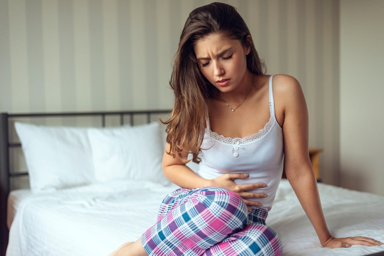 Starke Unterleibsschmerzen: Frau hält sich den schmerzenden Bauch