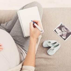 Babynamen: Schwangere Frau mit Ultraschall und Notizblock