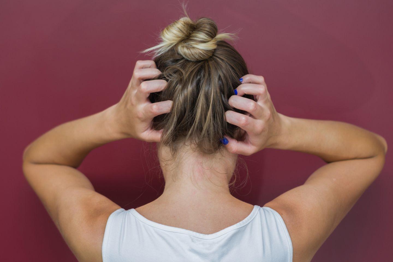 Trockene Kopfhaut: Ursachen und effektive Tipps: Frau fasst sich mit beiden Händen an den Hinterkopf