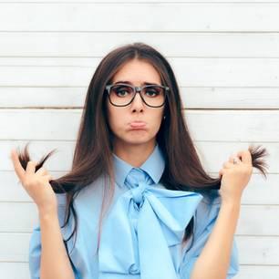 Haare brechen ab: Diese 4 Tipps helfen! Frau zieht einen Schmollmund, guckt unglücklich und hält ihre Haare fest