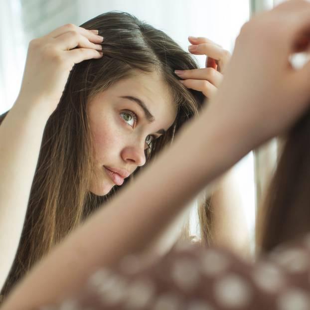 Pickel auf der Kopfhaut: Ursache, Tipps und Behandlung: Frau schaut in den Spiegel und begutachtet ihre Kopfhaut