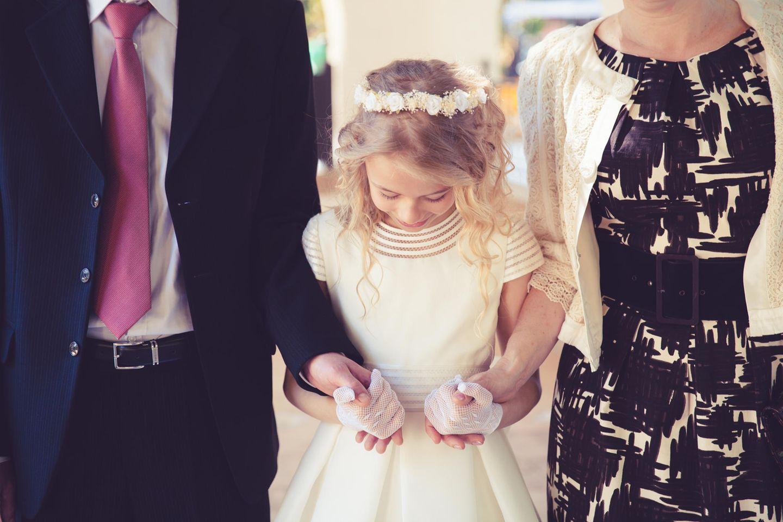 Sprüche zur Kommunion: Eltern halten Kind an der Hand zur Kommunion