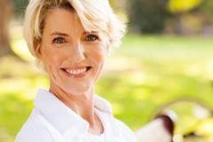 Kurzhaarfrisuren für Frauen ab 50: Frau mit kurzem Stufenhaarschnitt lächelt