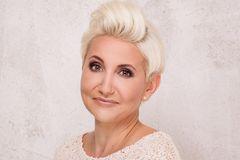 Kurzhaarfrisuren für Frauen ab 50: Frau mit Tolle im Haar lächelt leicht