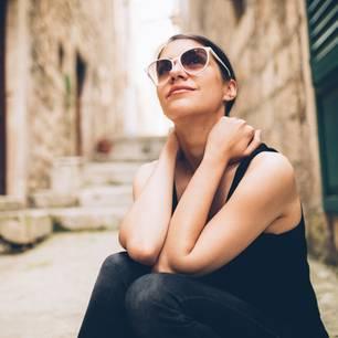 Horoskop: Frau trägt Sonnenbrille und sitzt auf einer Treppe