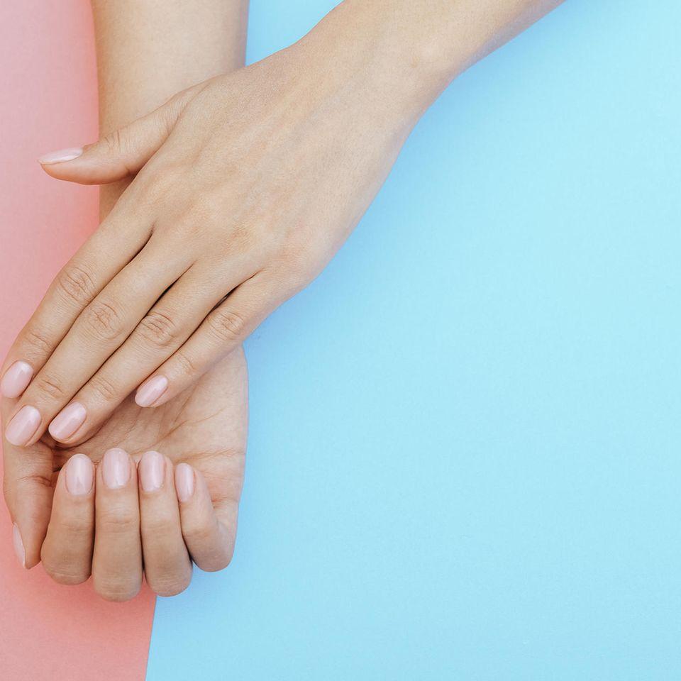 Eingerissene Nagelhaut: Zwei Hände mit rosafarbenen Fingernägeln