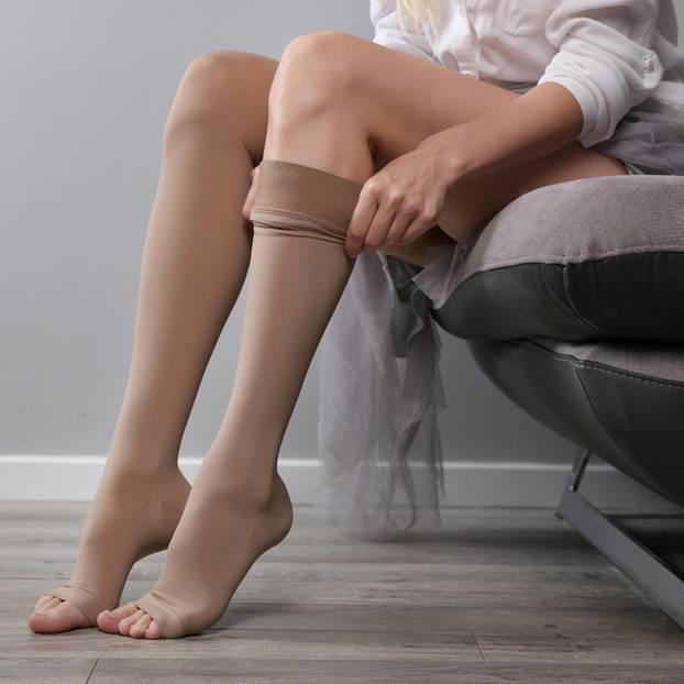 Thrombose Anzeichen: Frau zieht Thrombose-Strumpf an