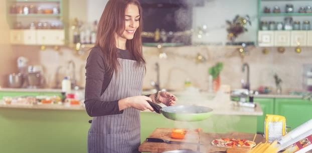 Frau mit Pfanne in der Hand kocht