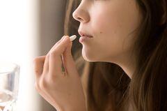 Medikamente bei Frauen: Frau nimmt eine Tablette
