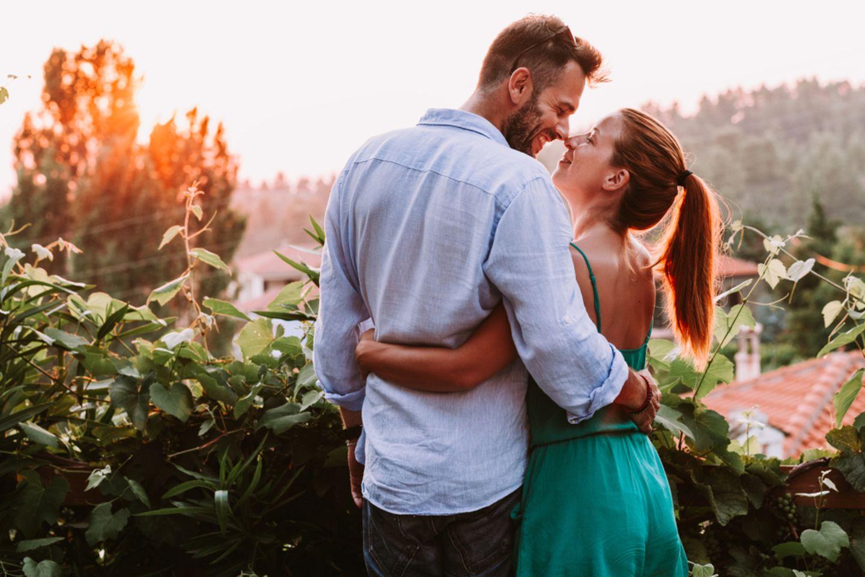 Horoskop: Pärchen steht auf einem Balkon und schaut sich verliebt in die Augen beim Sonnenuntergang
