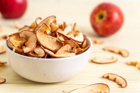 Apfelringe trocknen: Apfelchips in einer kleinen Schale, im Hintergrund ein roter Apfel